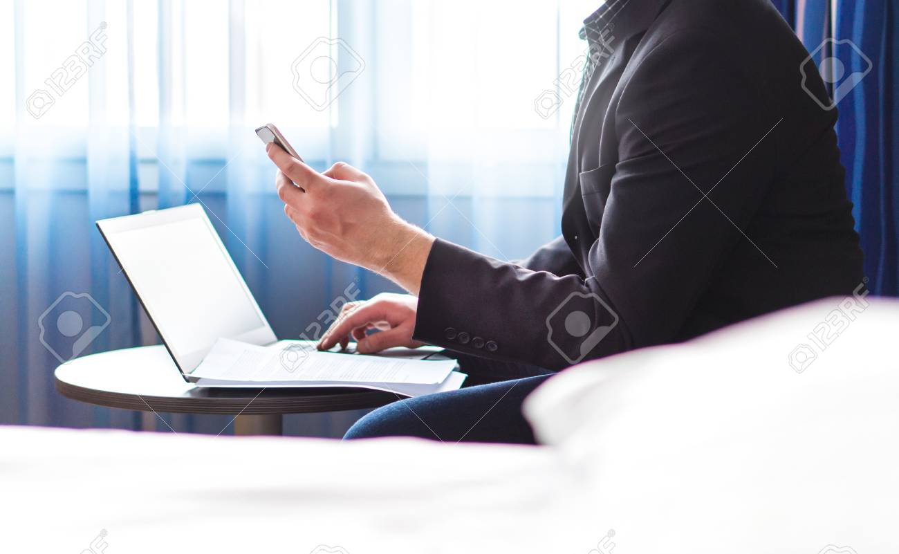 Business man in hotel room with smartphone and laptop. Businessman reading emails or using social media. Remote work during business trip. Making phone call. Elegant man in suit using hotel wifi. - 95852795