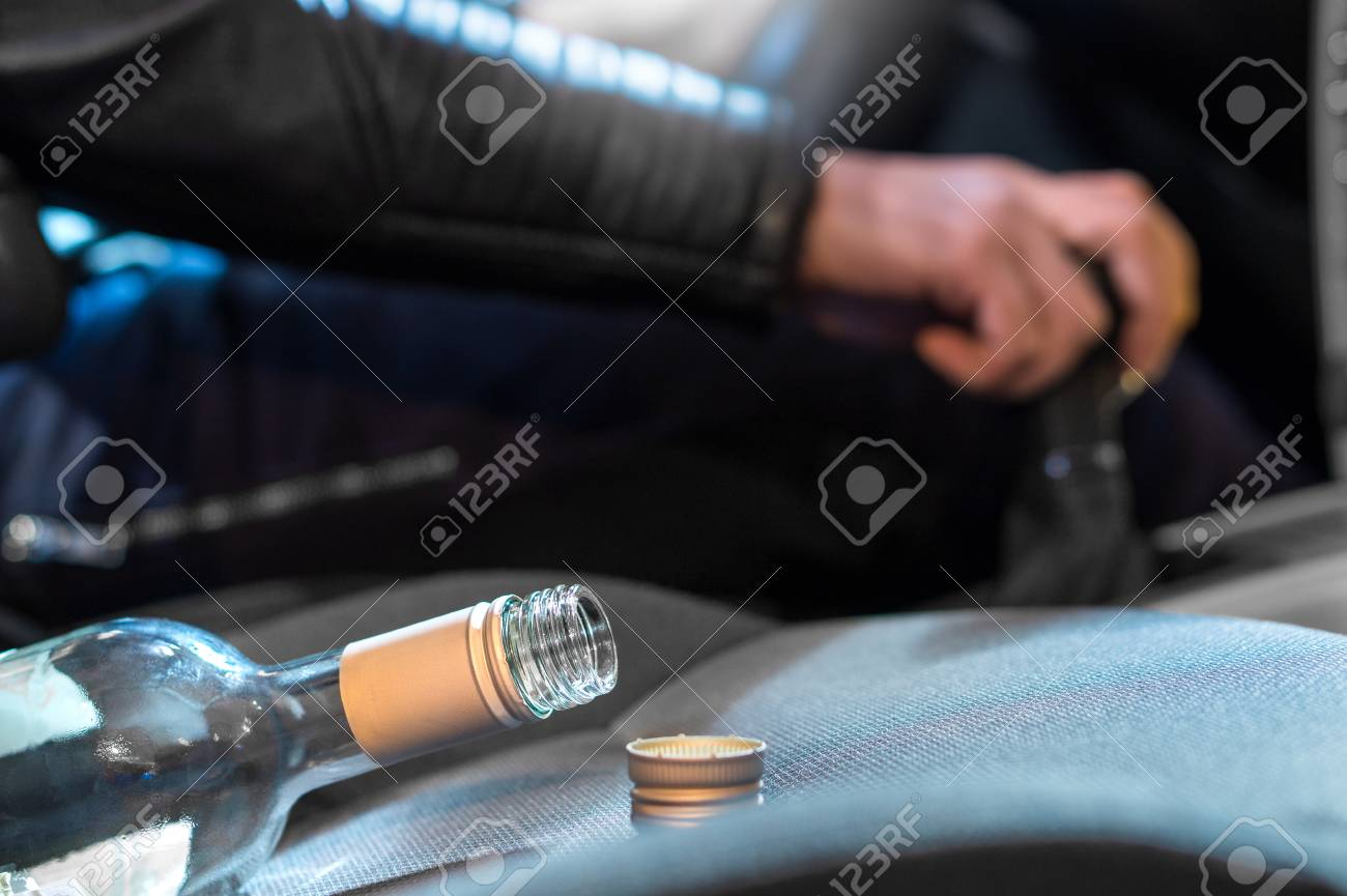 Drunk driving concept. Young man driving car under the influence of alcohol. Hand on gear stick. Close up of empty bottle of wine on front seat. Traffic safety risk. - 95742758