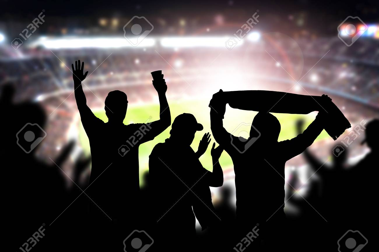 Friends at football game in soccer stadium. Crowd cheering and celebrating a goal in arena during match. Silhouette people in live sport audience having fun. - 95742763