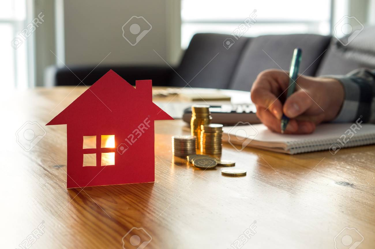 Man counting house price, home insurance cost, property value or rent on paper. Realtor or real estate agent writing offer. Mortgage, saving and buying apartment. Money and small building on table. - 107378031