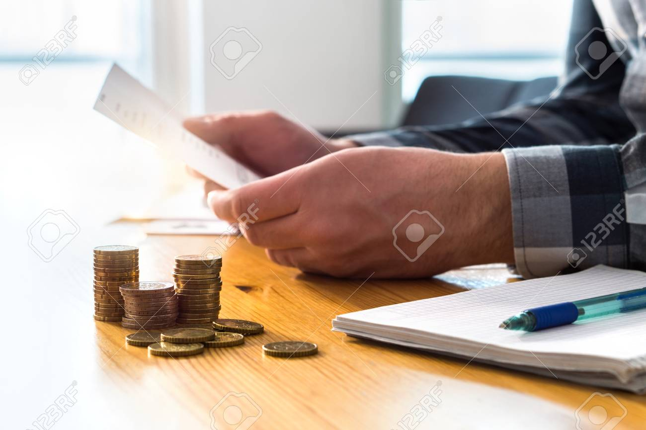 Man reading bank statement, check reminder, tax refund document, phone bill, or financial letter. Home or health insurance price and cost concept. Person holding paper invoice in hand. - 107378052