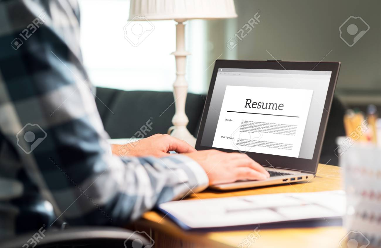 Man writing resume and CV in home office with laptop. Applicant searching for new work and typing curriculum vitae for application. Job seeking, hunt and unemployment. Mock up text in computer screen. - 107389514