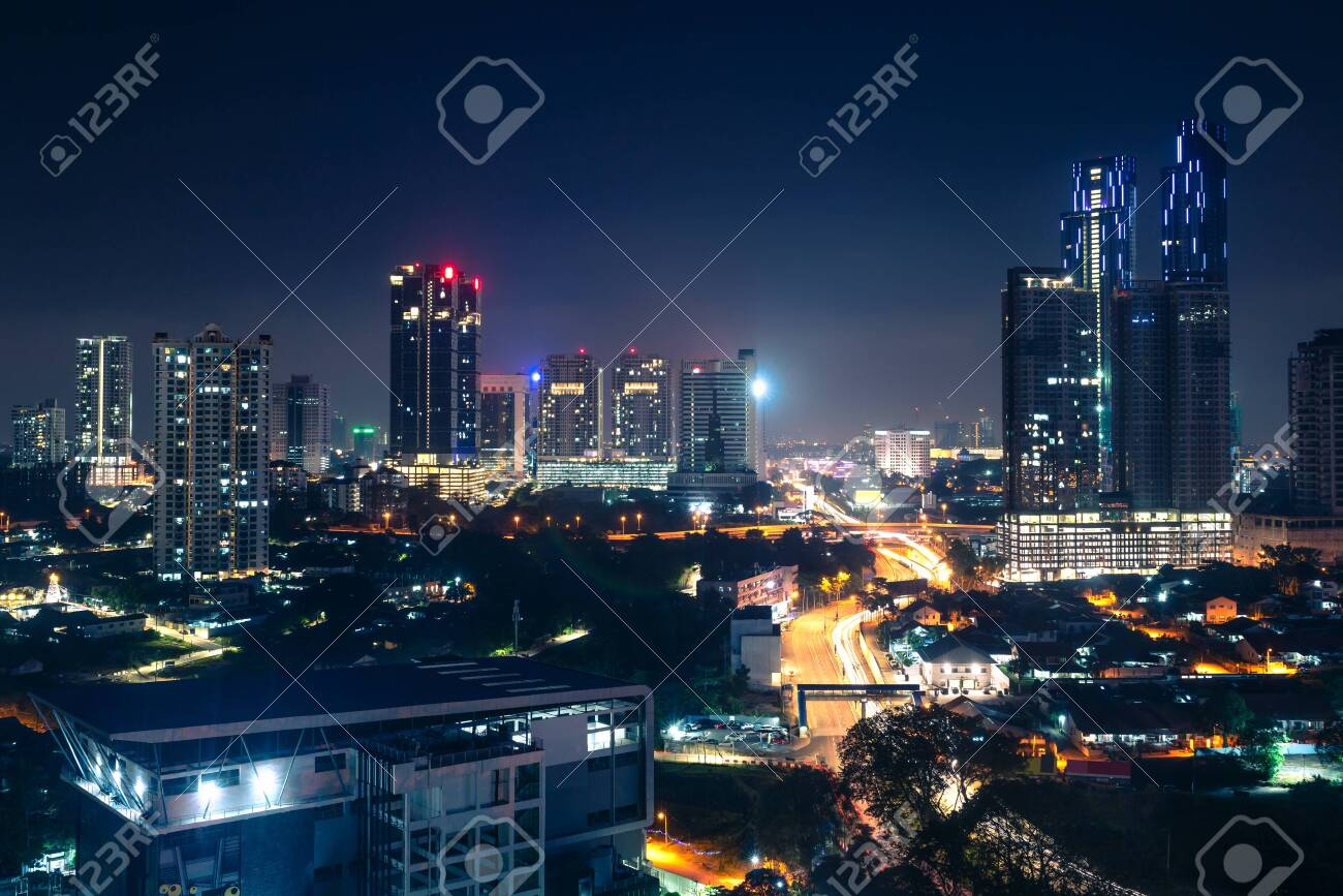 Johor Bahru, Malaysia, at night. Malaysian city with traffic on highway and modern business buildings and hotels in downtown. Scenic urban skyline and cityscape. Aerial view. - 141631341