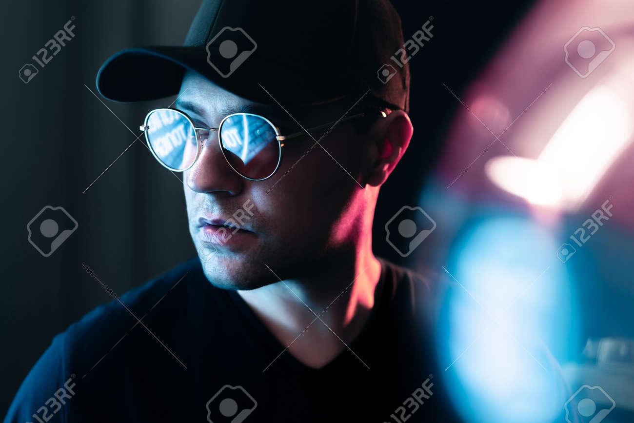 Neon light in glasses of a man. Futuristic cyber studio portrait. Techno glow and vibrant cyberpunk color. Male model with sunglasses in fluorescent illumination. Future mood. Urban fashion style. - 172373394