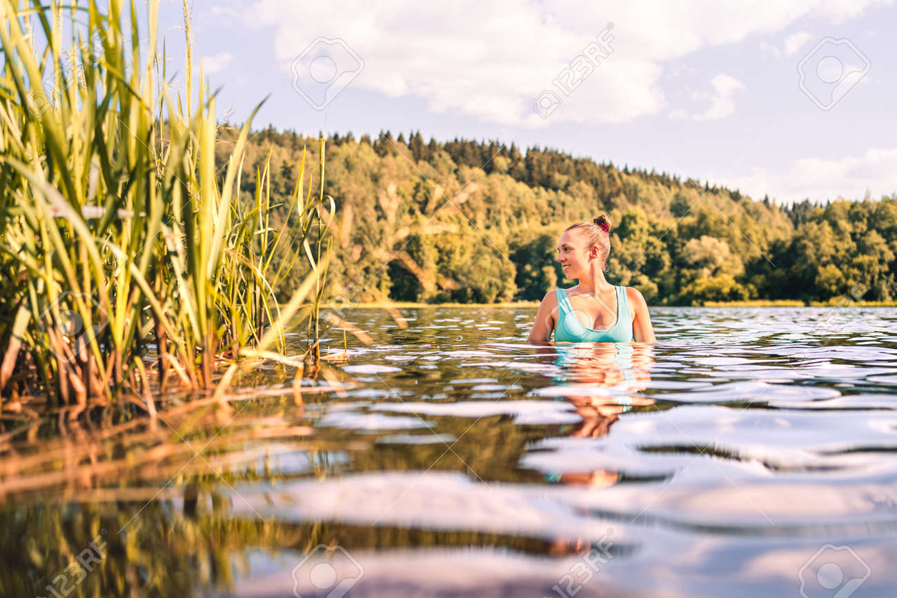 Lake in Finland. Happy smiling woman swimming in water summer. Finnish nature at sunset. Pretty girl in swimsuit or bikini enjoying a peaceful weekend or vacation outside at the beach in Scandinavia. - 172293306