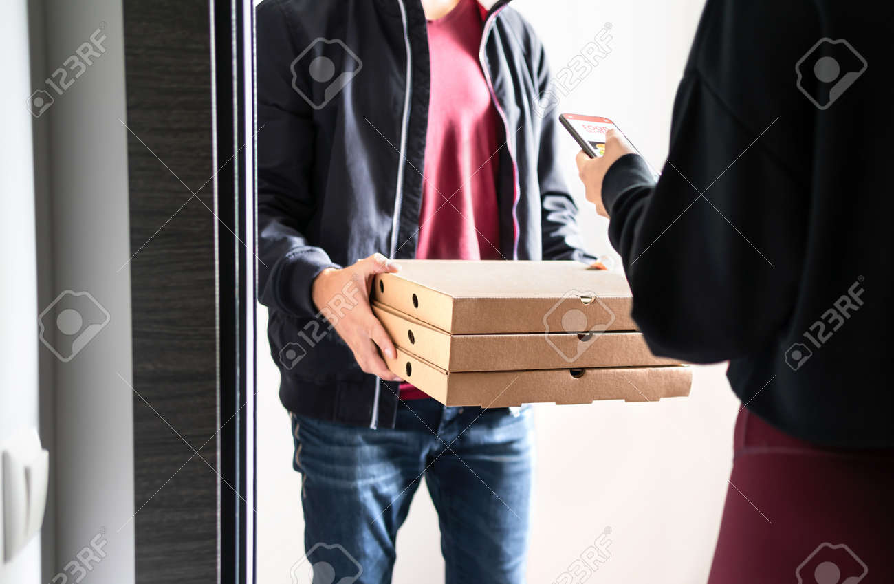 Pizza delivery to door. Online order with phone. Customer using smartphone mobile app to pay, tip or give rating and review. Home deliverer holding fast food boxes. Restaurant deliver service. - 173105960
