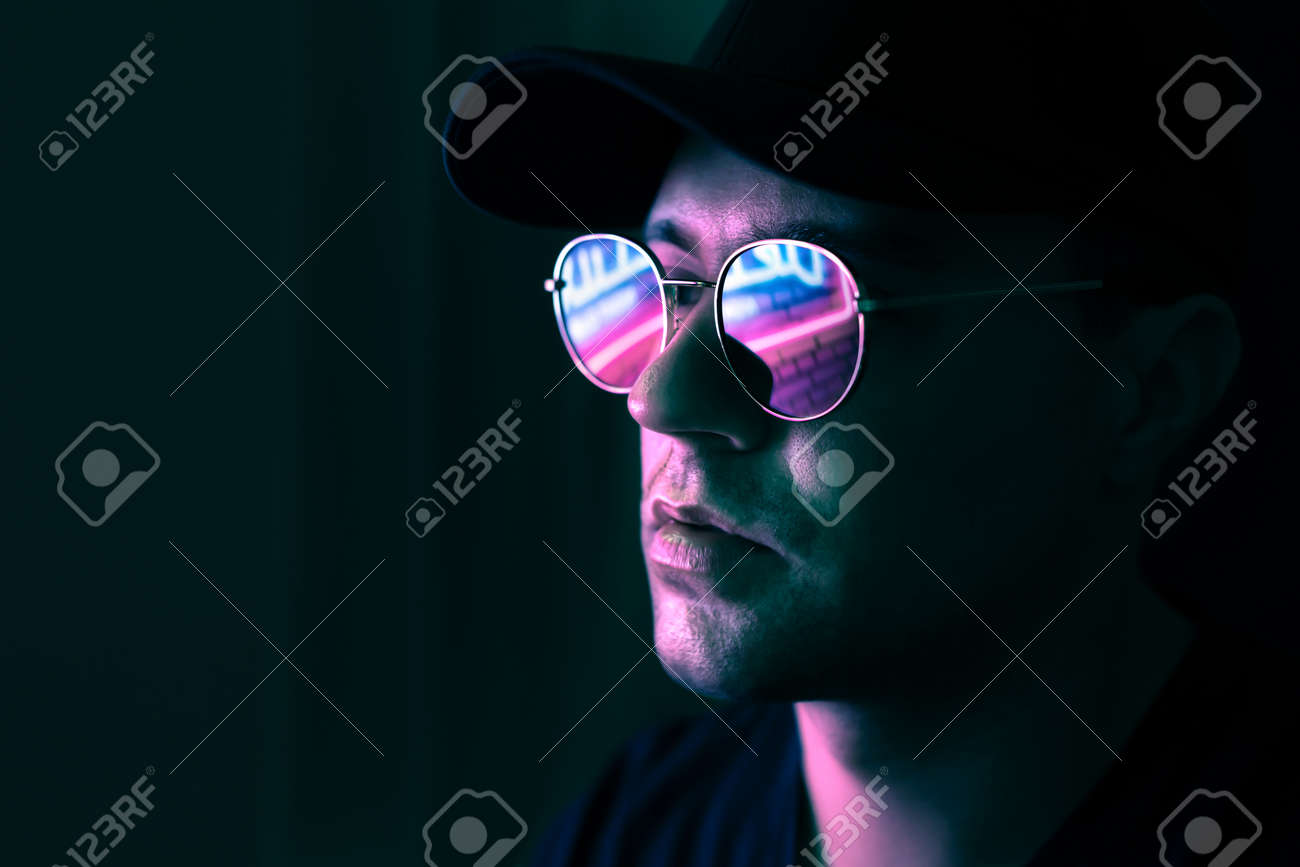 Neon reflection in glasses. Man in fluorescent light from city led sign. Mysterious cool model in futuristic cyberpunk portrait. Guy in sunglasses. Techno rave party disco art. Dark black background. - 173105406