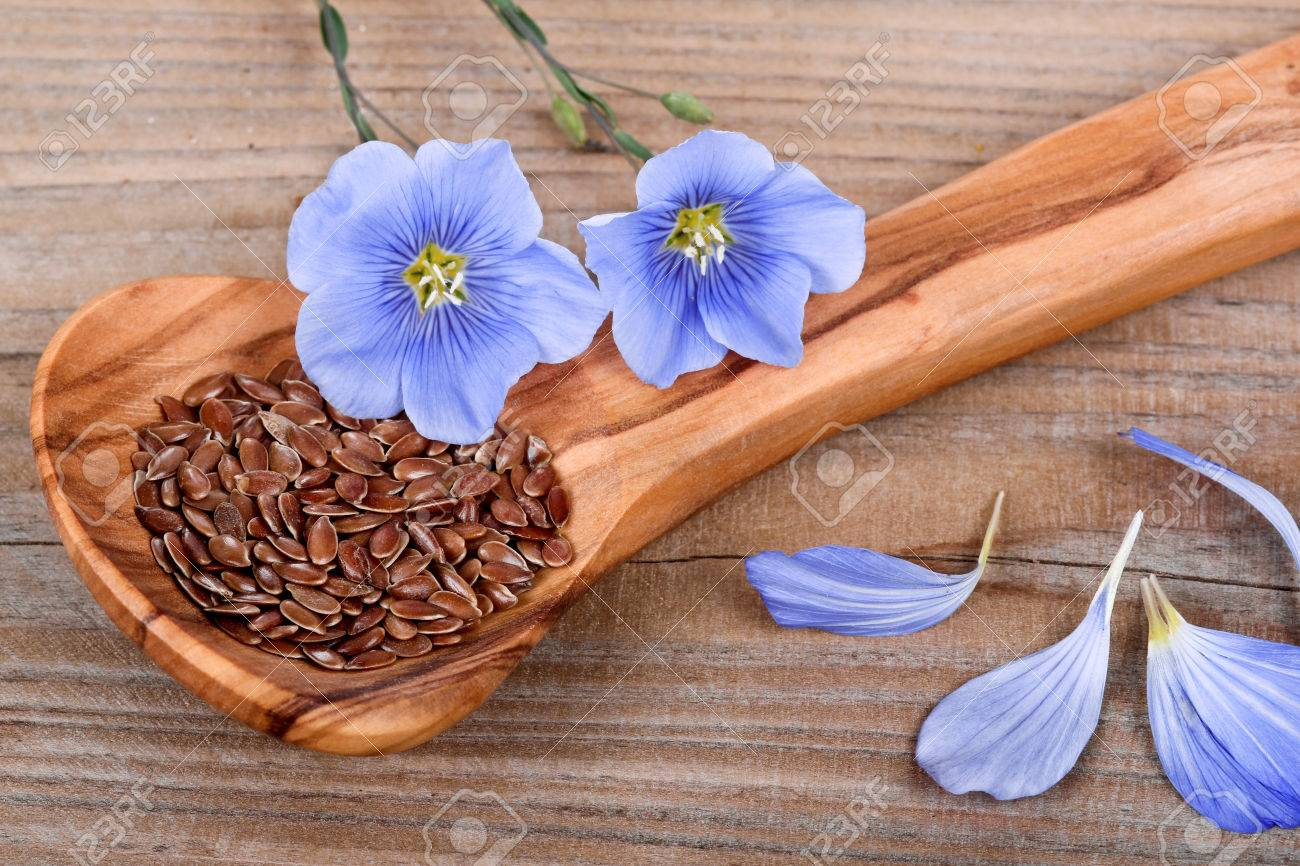 Wooden spoon with flaxseed and linum blossoms - 32926509