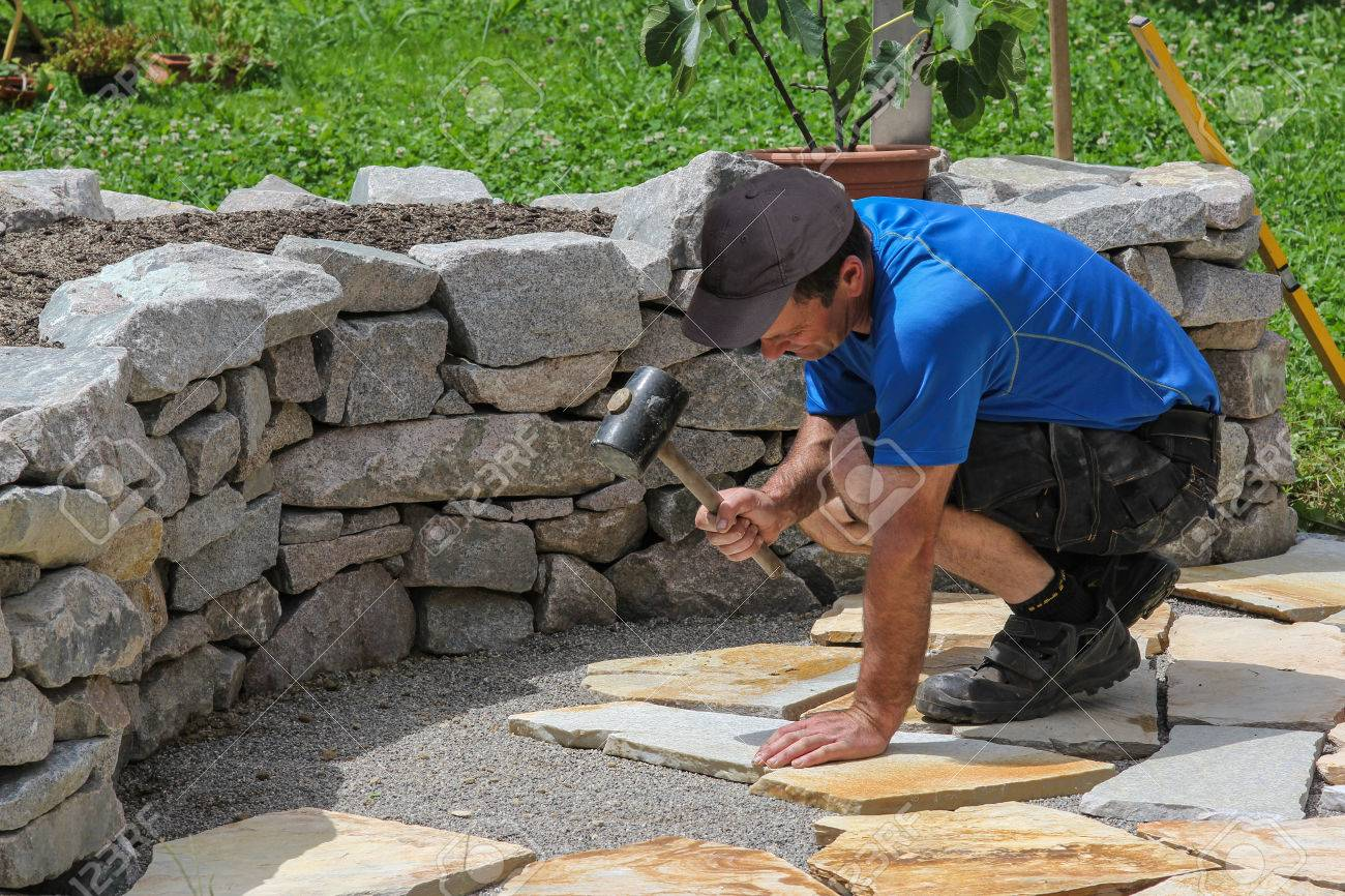 A worker laid tiles in the garden - 37566509