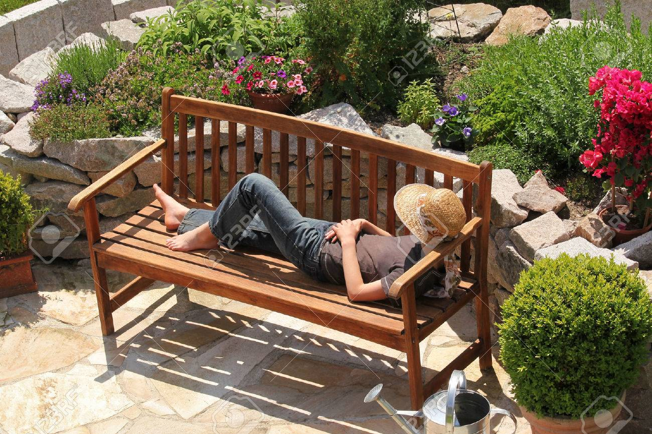 Relaxing on a garden bench - 37567441