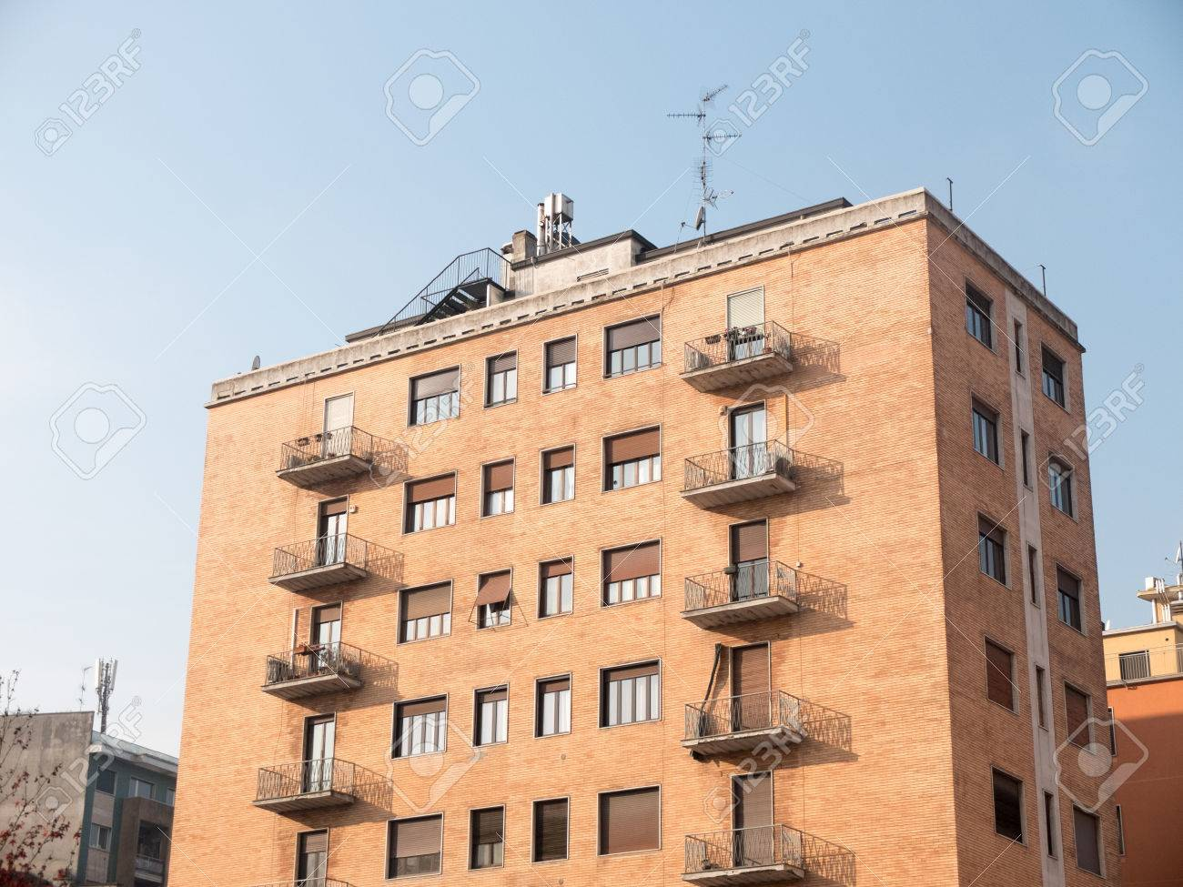 Low Rise Residential Apartment Building With Small Balconies And Brick  Facade Illuminated By Bright Sunlight On