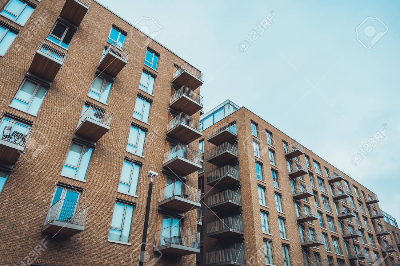 Low Angle View Of Modern Brick Residential Apartment Buildings With Small  Balconies And Long Windows Stock
