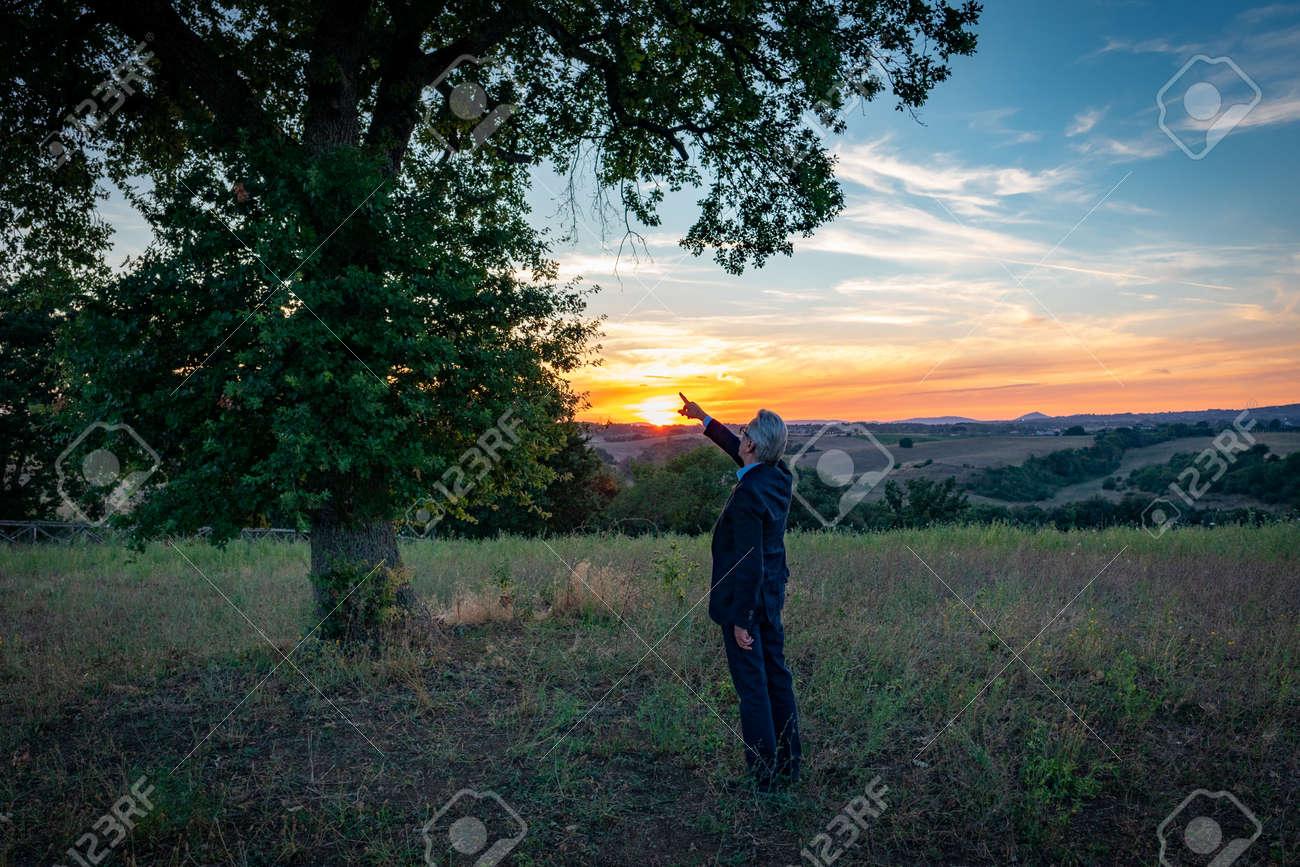 Senior botanist talking with the magic tree at sunset - 163714004