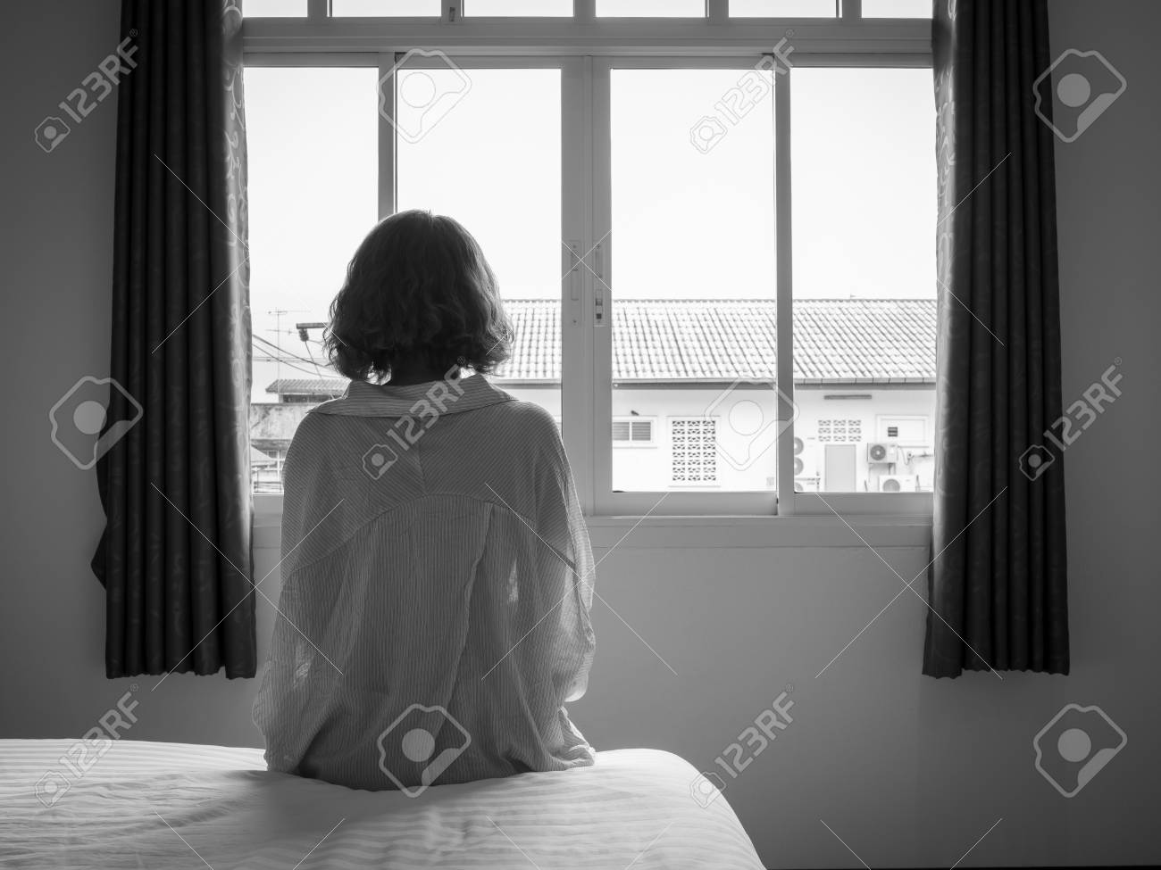 106546980 woman short hair sitting on the white bed in hotel room lonely woman looking out the window alone in jpg