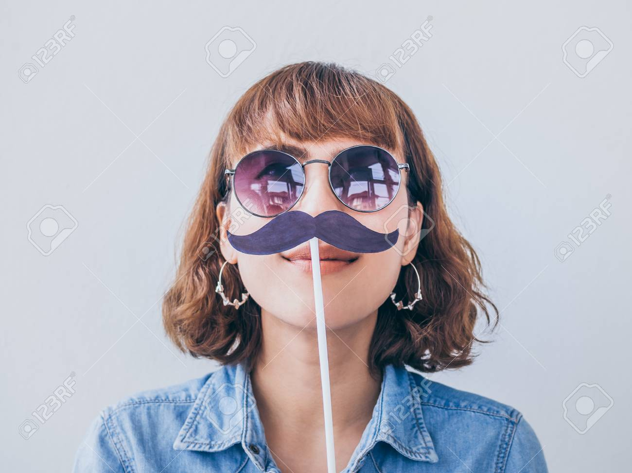 fe4acc886d Beautiful asian woman short hair wearing blue jeans shirt and sunglasses  smiling with fake mustache isolated