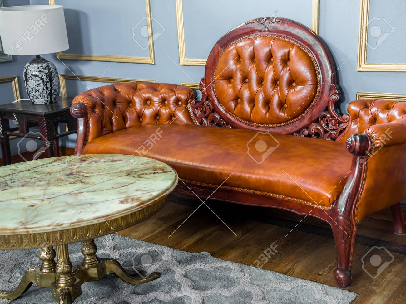 Vintage luxury red brown leather sofa with marble and brass round..