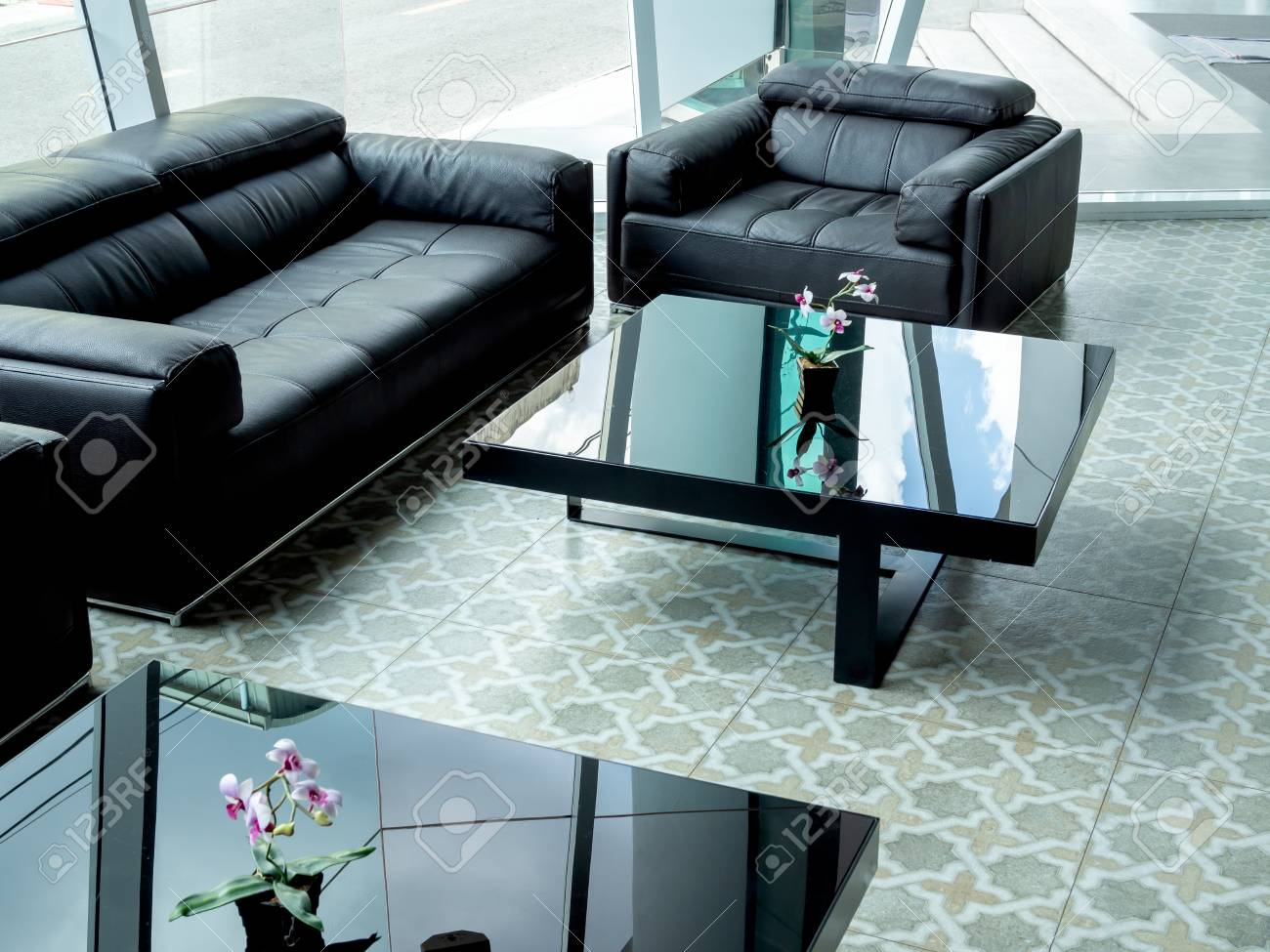 Modern black leather sofa and black glass table on tile flooring..
