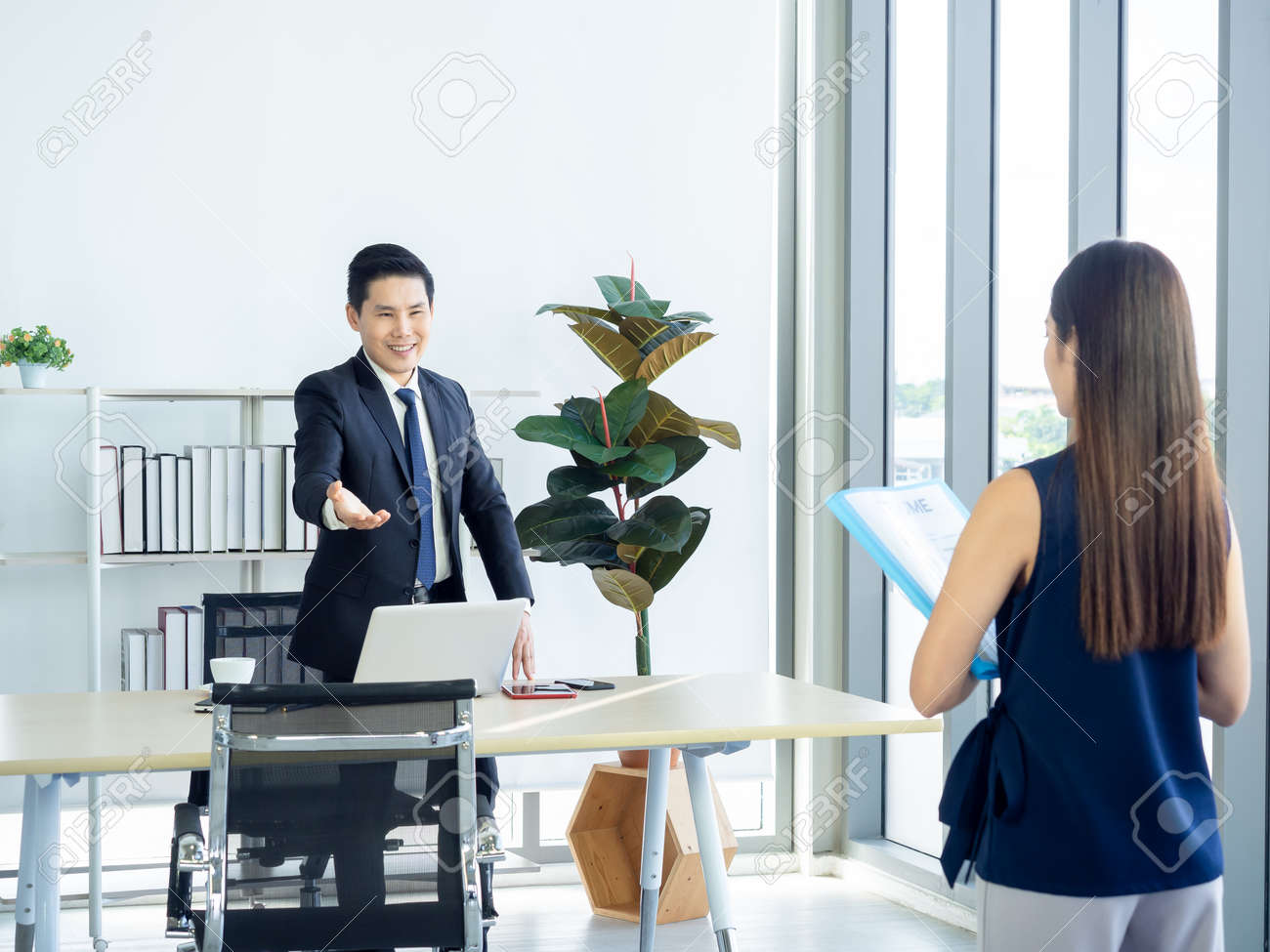 Asian businessman, boss in suit making hand gesture to invite young woman holding resume in the job interview to sit down on the chair near huge glass window in manager room in modern office interior. - 158176040