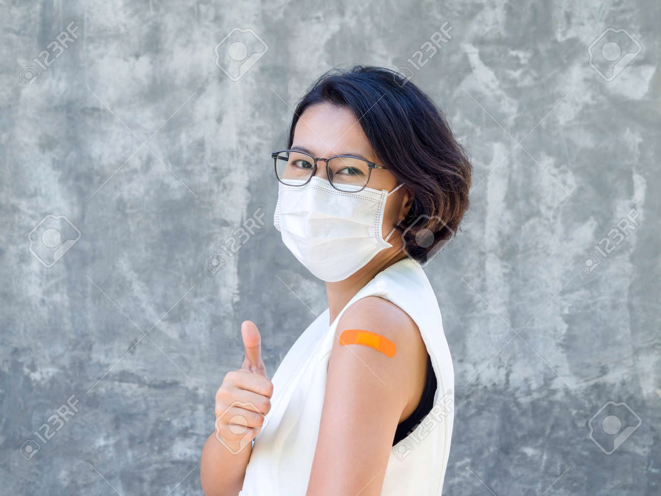 Vaccinations, bandage on vaccinated people's arm concept. Happy business Asian woman wearing white blazer vest, face mask, glasses showing orange bandage and thumb up, after vaccination treatment. - 170936932