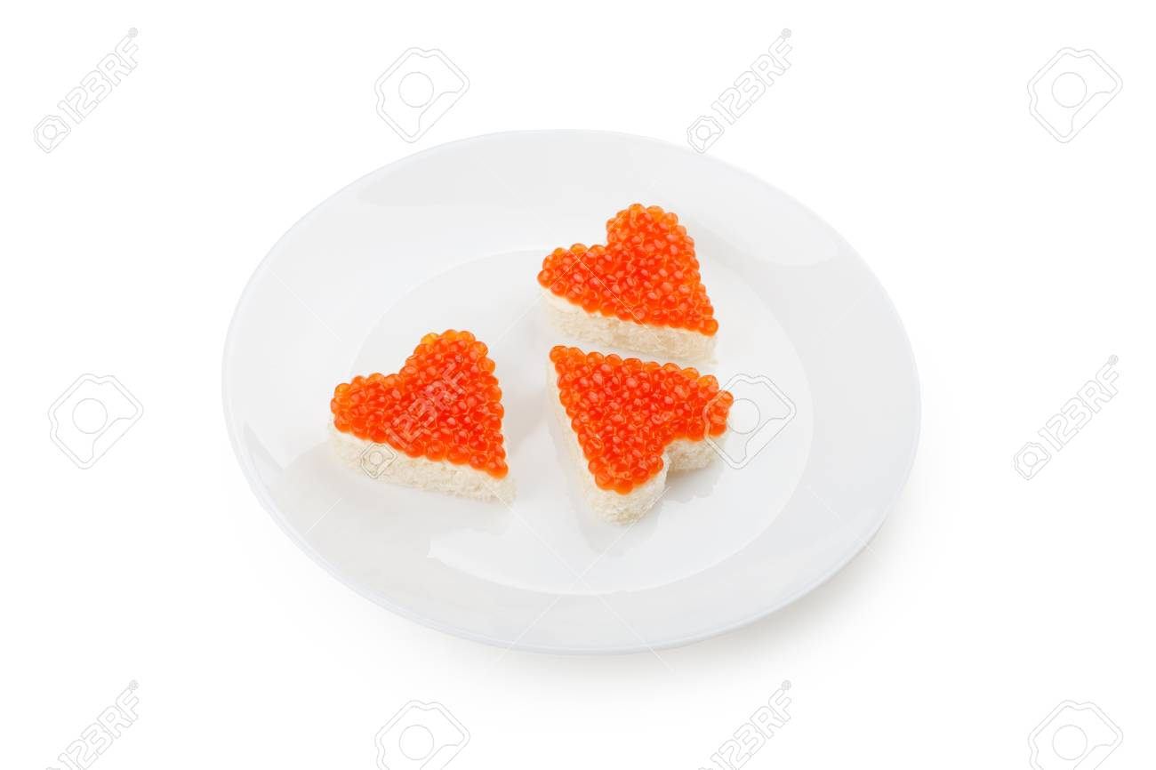 Three sandwiches with red caviar in the shape of heart lie on a white plate isolated on white background. - 106004593