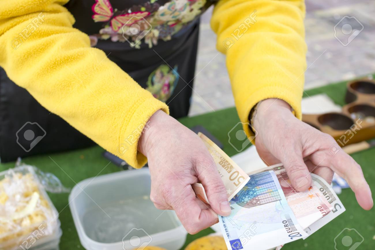Woman seller returns change in euro in the market Stock Photo - 18587158