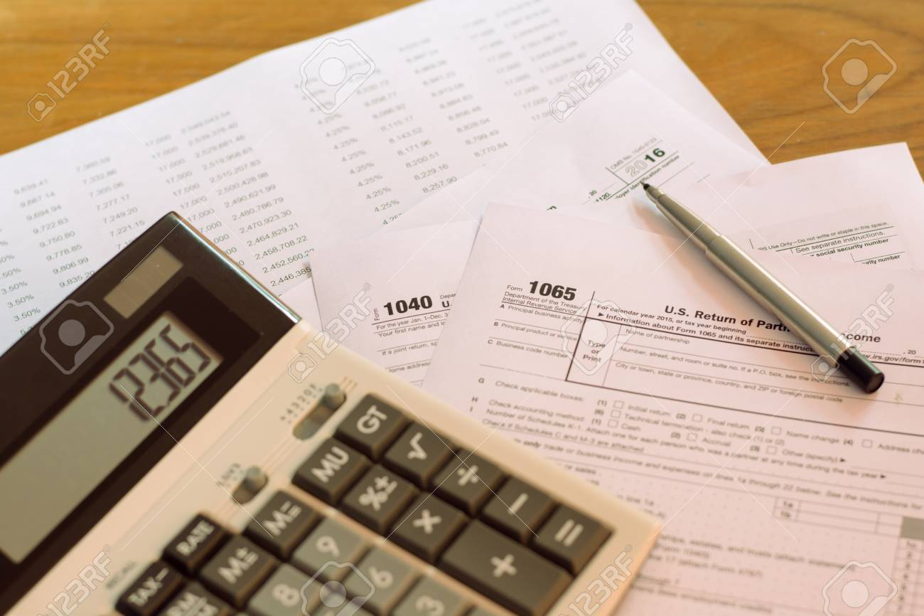 form 1065 calculator  US tax form with pen and calculator selective focus / taxation..