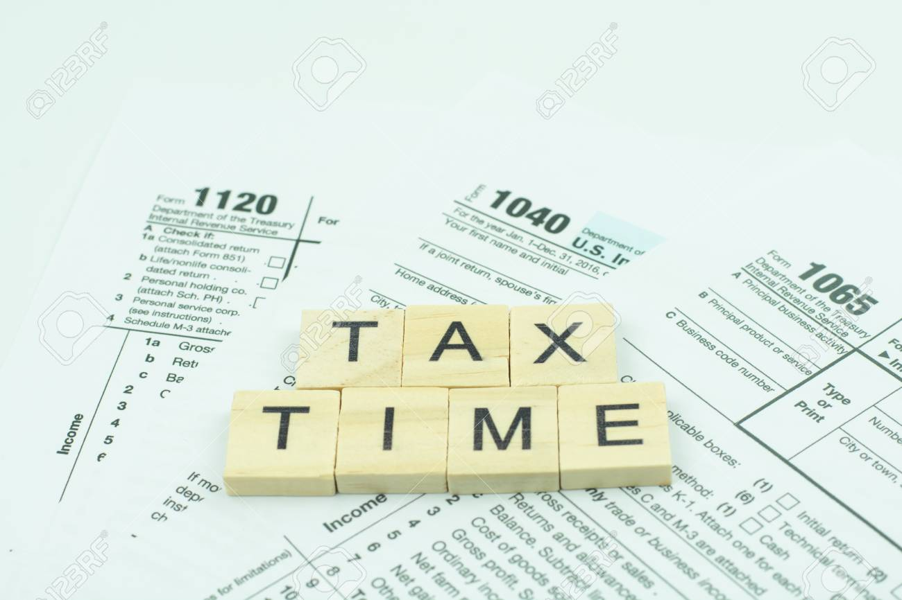 Tax Time text wooden block with on U S  tax form