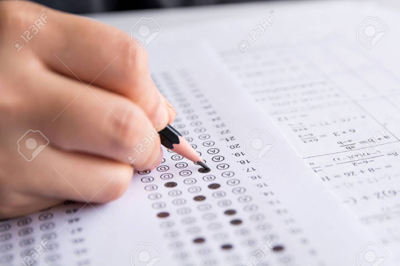 Students hand holding pencil writing selected choice on answer sheets and Mathematics question sheets. students testing doing examination. school exam - 105015355
