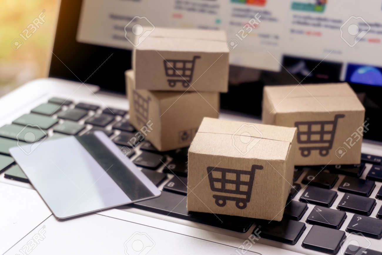 Online shopping - Paper cartons or parcel with a shopping cart logo and credit card on a laptop keyboard. Shopping service on The online web and offers home delivery. - 159380035