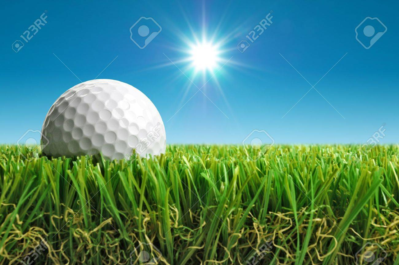 close up of golf ball in grass with sun in background stock photo