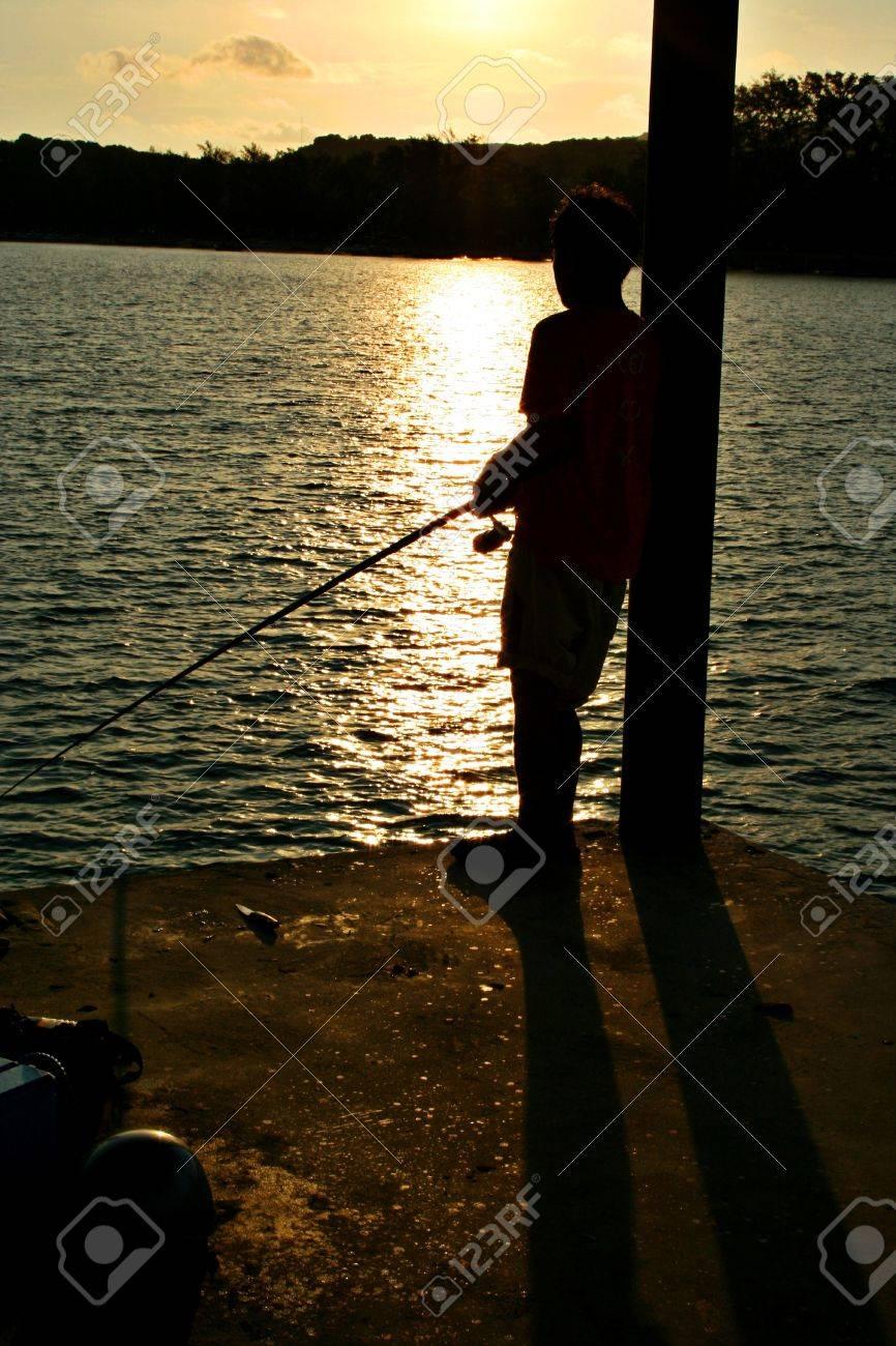 A distraught young man fishing at Rawai Beach, Phuket, Thailand - 8055669