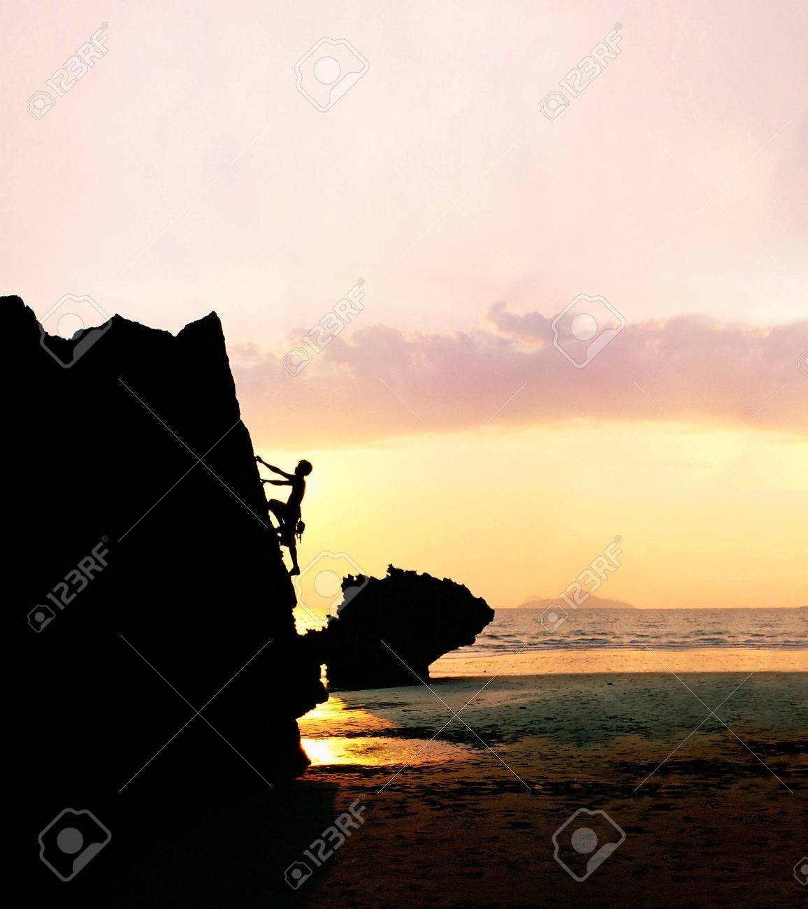 Silhouette of a man rock-climbing at sunset. - 8863131