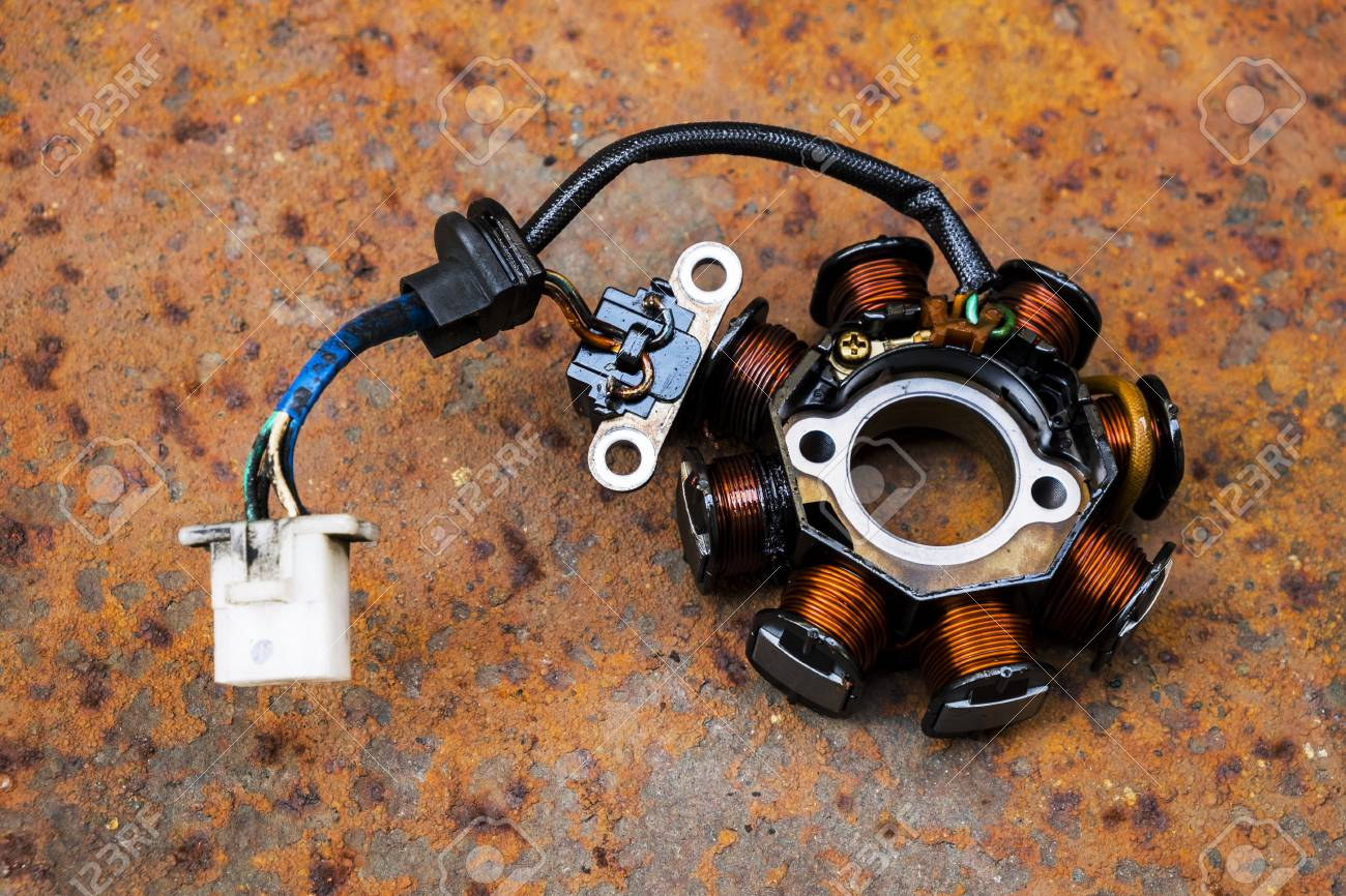 Used Motorcycle Stator on a Rusty Metal Sheet Background