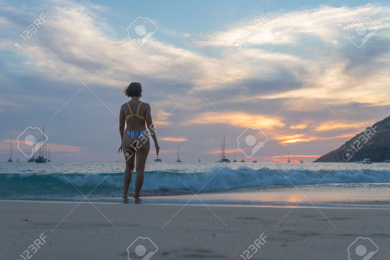 lady walking on the beach in sunset - 166145770