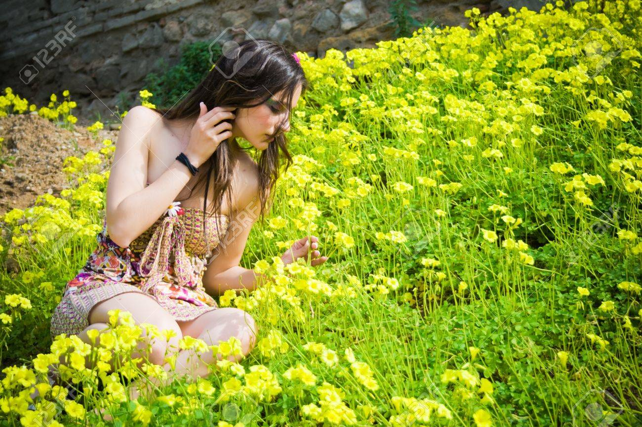 beautiful young hippie sitting among the flowers and smelling one of them Stock Photo - 12014269