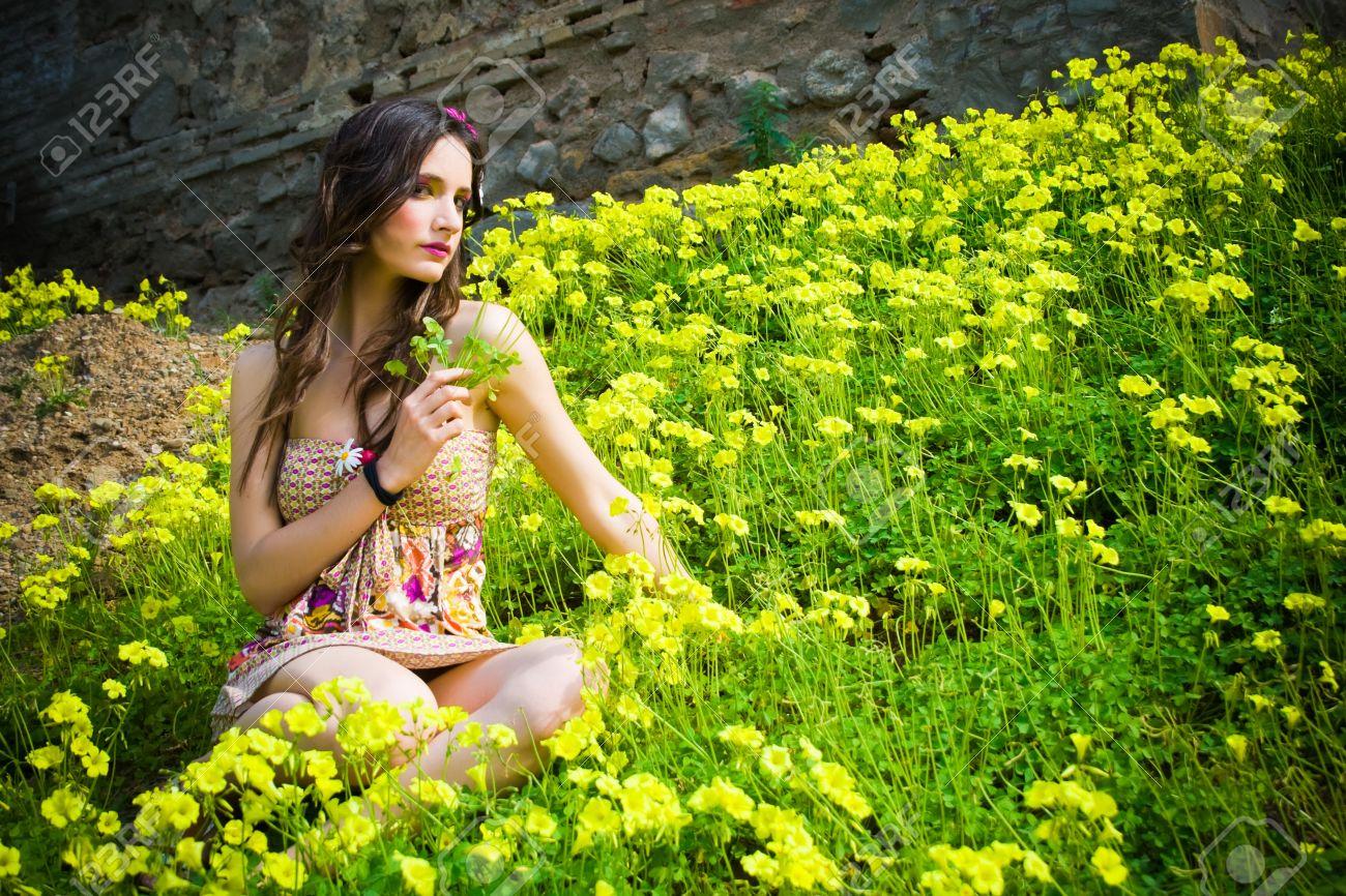 Beautiful hippie girl sitting in a field of flowers with a flower beautiful hippie girl sitting in a field of flowers with a flower in her hand stock izmirmasajfo