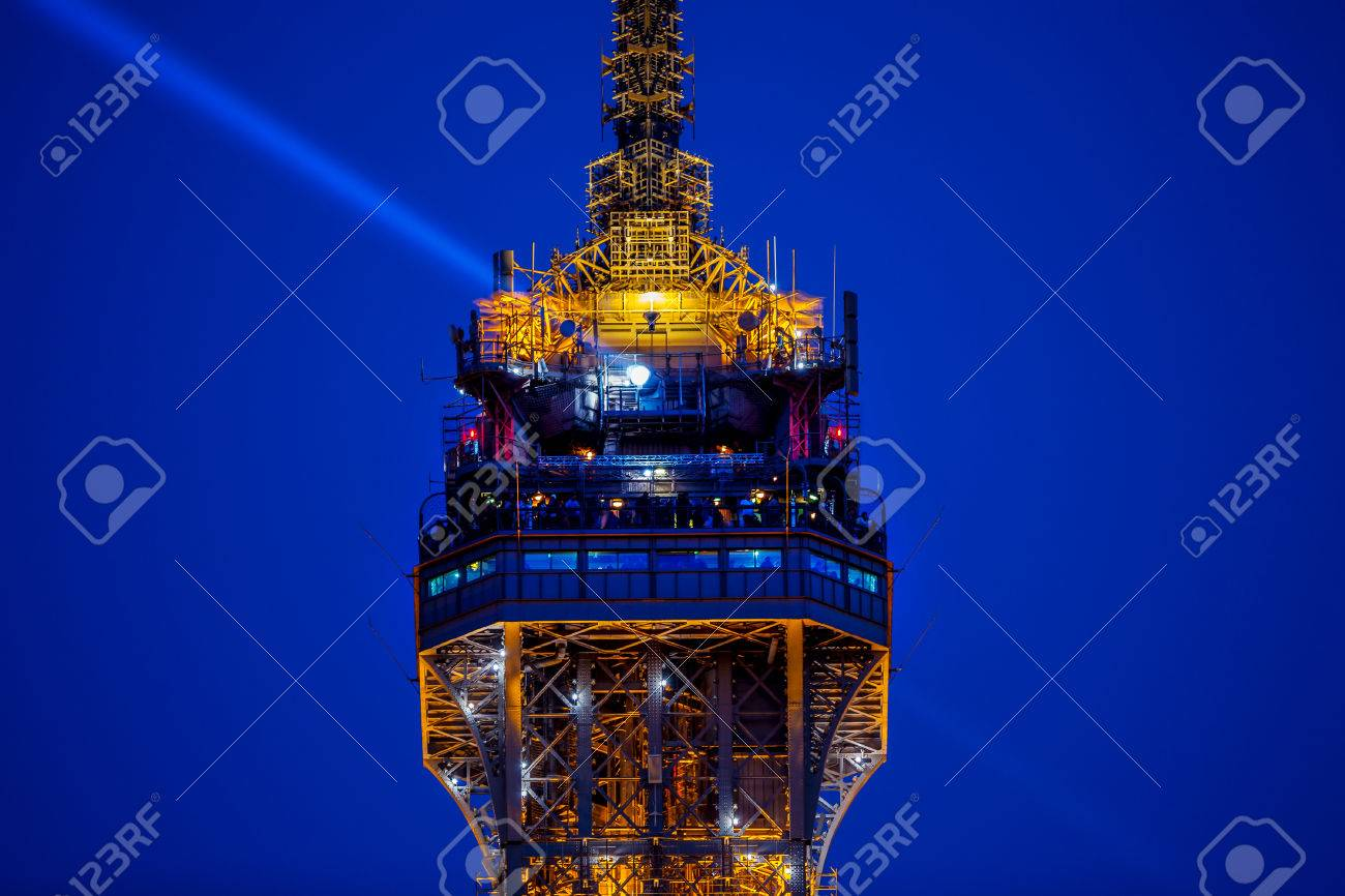 People At The Top Of Eiffel Tower And A Light Beam In Sky Stock