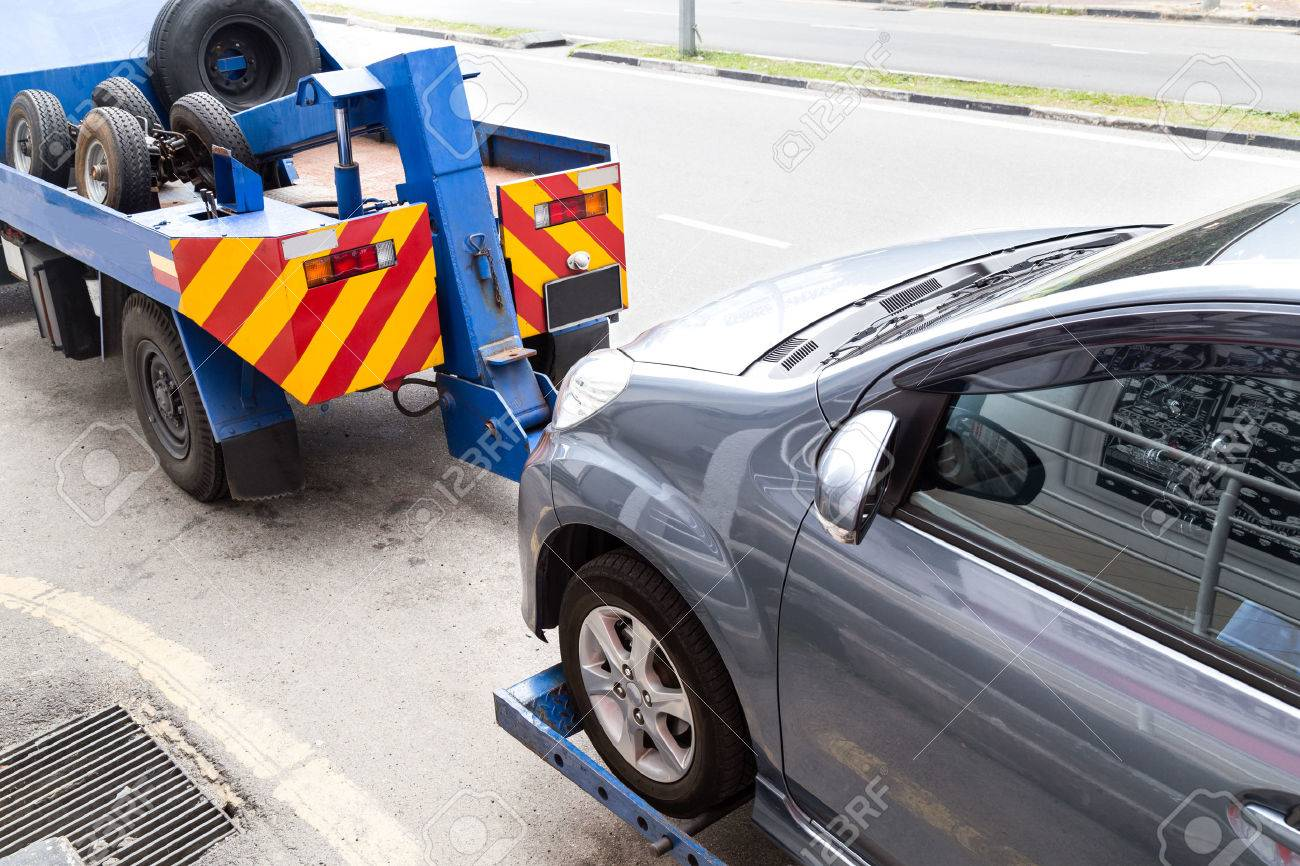 Tow truck towing a broken down car on the street. - 46986761