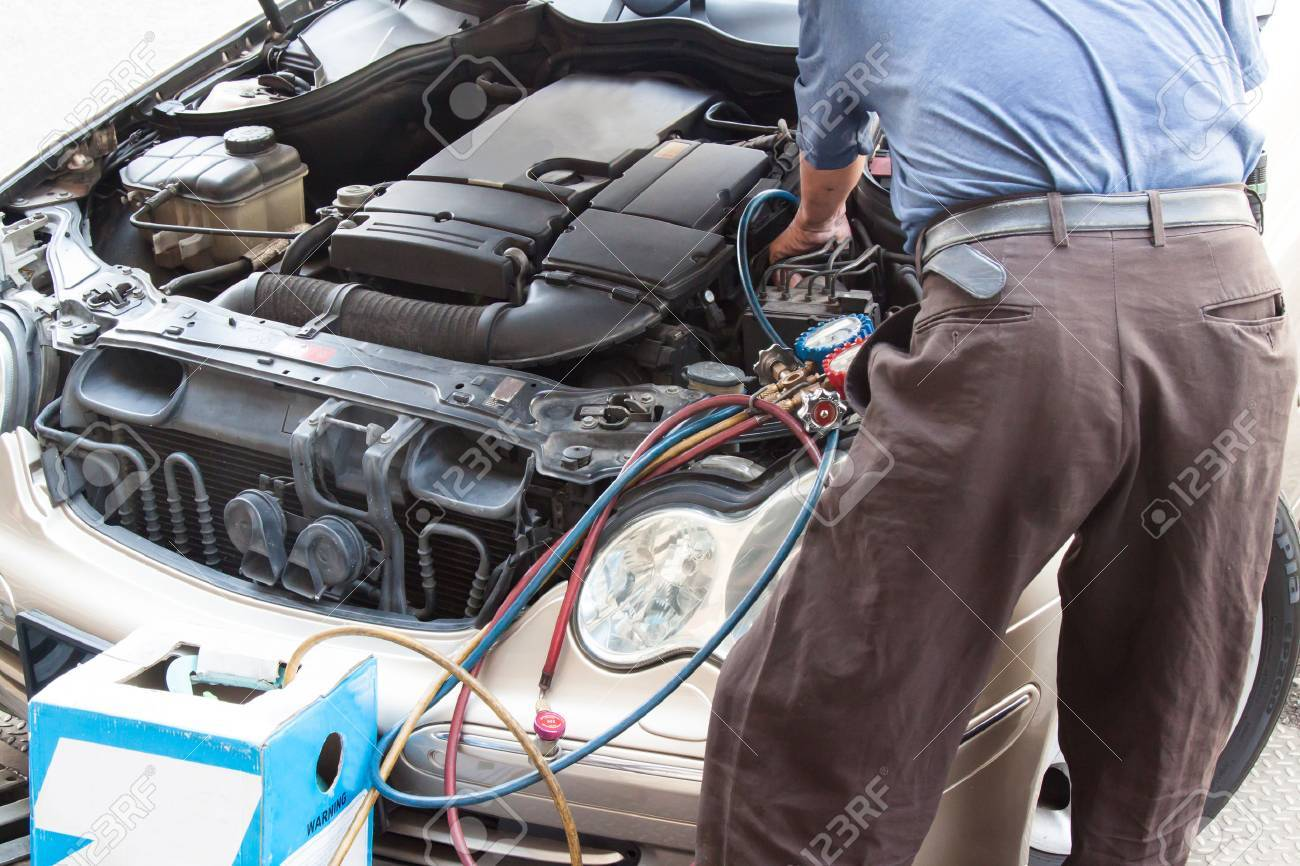Mechanic With Manometer Filling Gas Into Auto Vehicle Air-condition ...