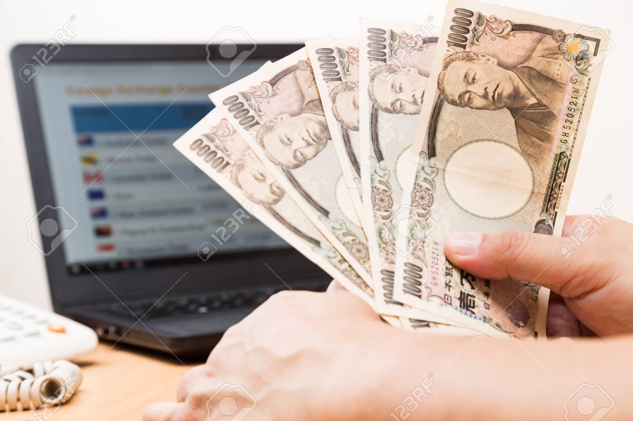 Main tenant le yen japonais au bureau avec écran dordinateur