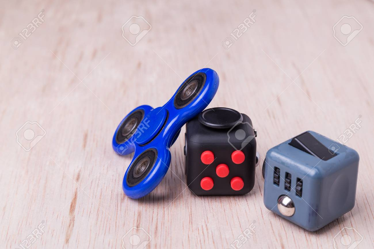 Fidget Spinner And Cube The Latest Stress Relieving Craze On Table Top Stock Photo