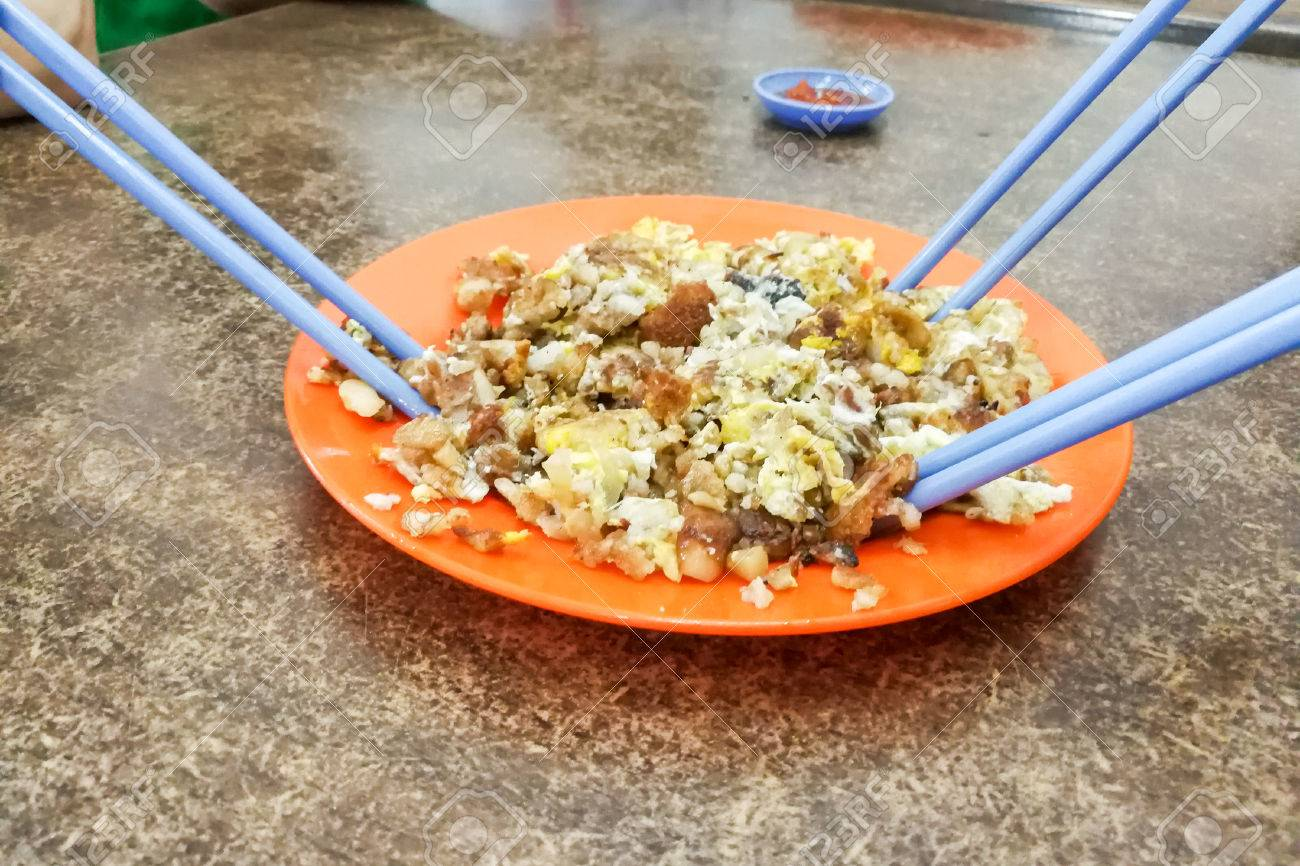 Plate of fried carrot cake or kueh kak with people holding chopsticks
