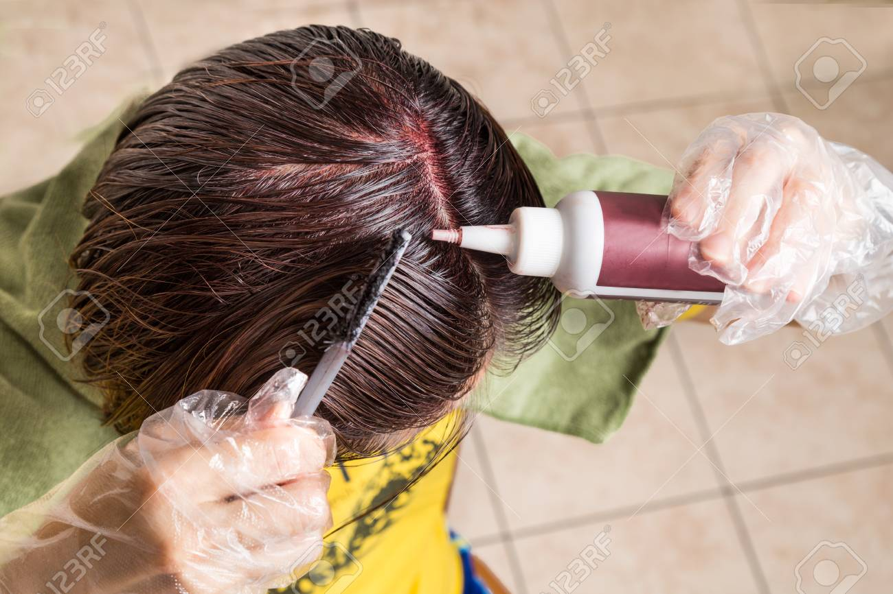 Woman Attempting To Apply Chemical Hair Color Onto Scalp. Self ...