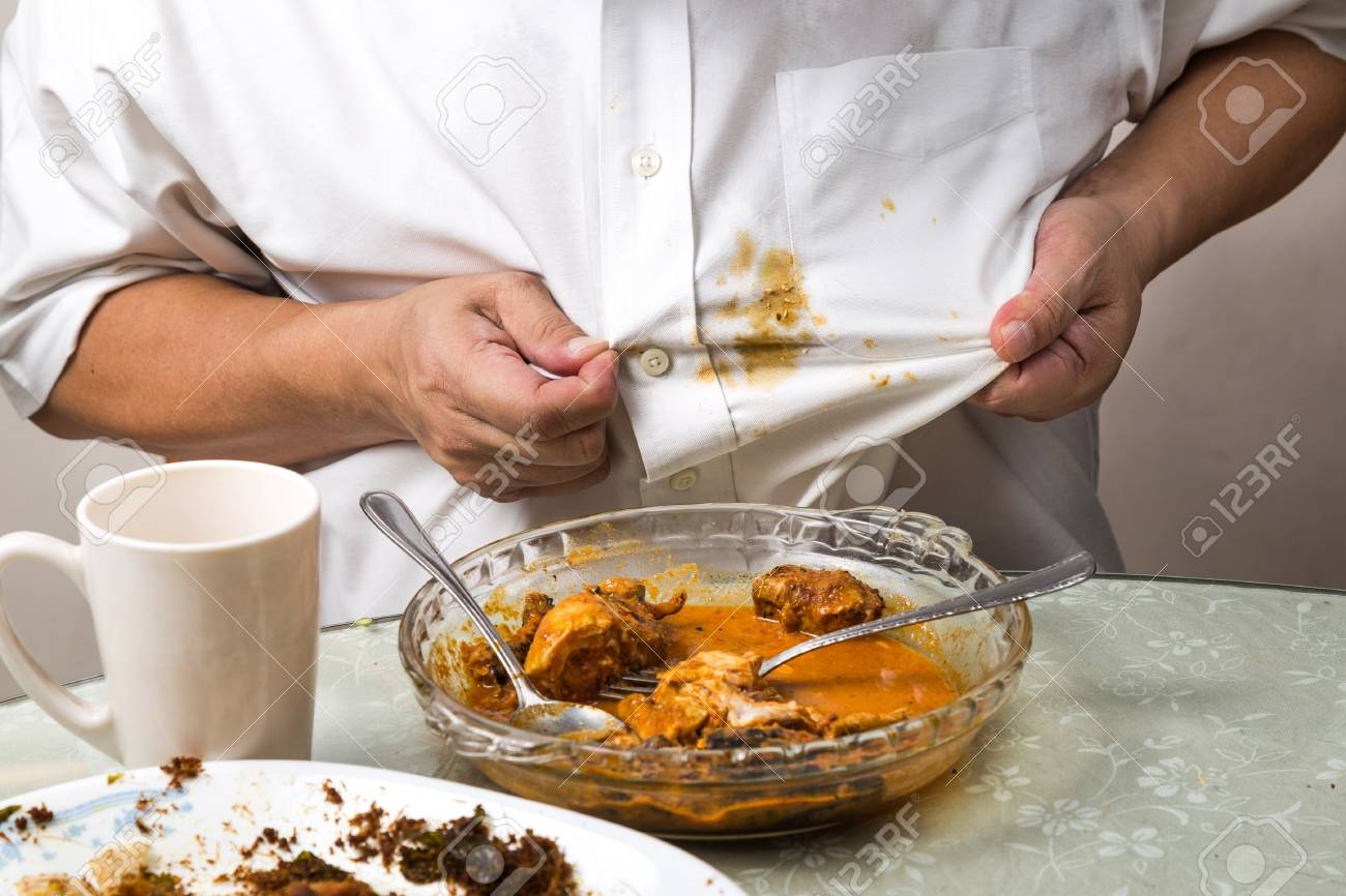 Person accidently spilled curry stain onto white shirt and reacted with frustration. - 95558572