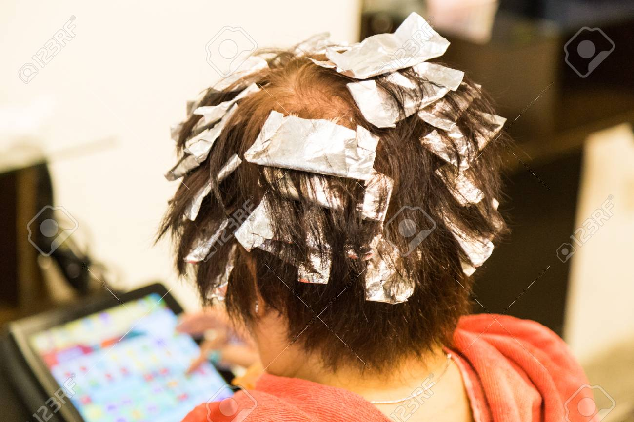 Person\'s hair wrapped with aluminum foil during chemical color..