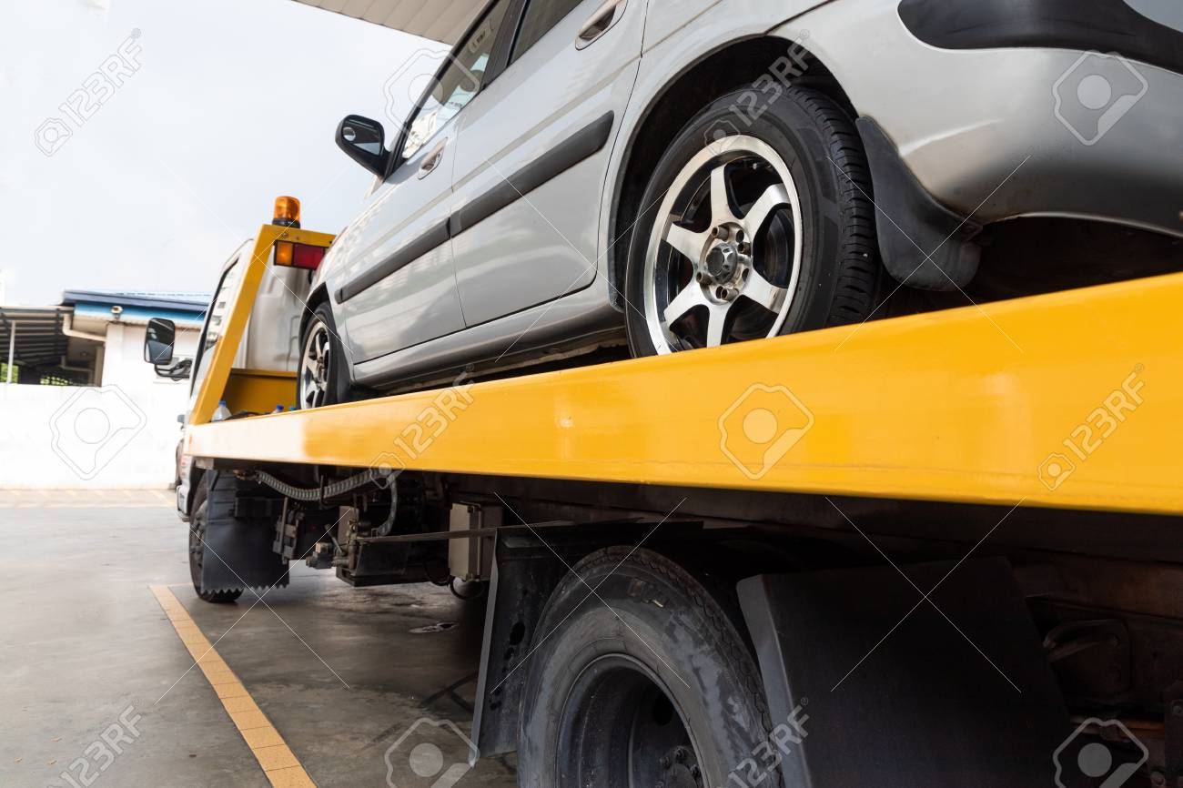 Broken down car on flatbed tow truck being transported to garage workshop for repair - 123093151