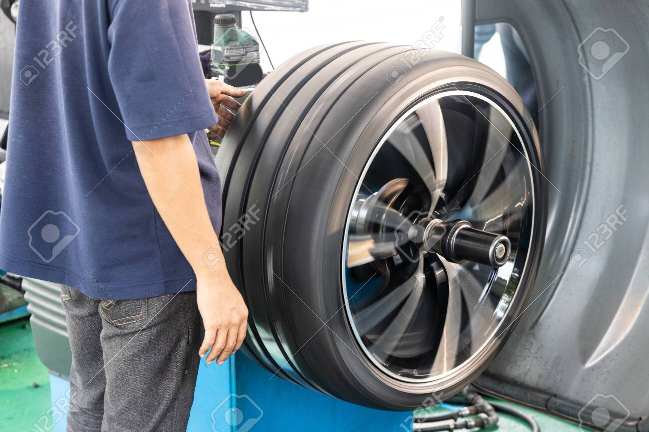 Series of worker balancing tire with wheel balancing machinery in workshop - 129754520