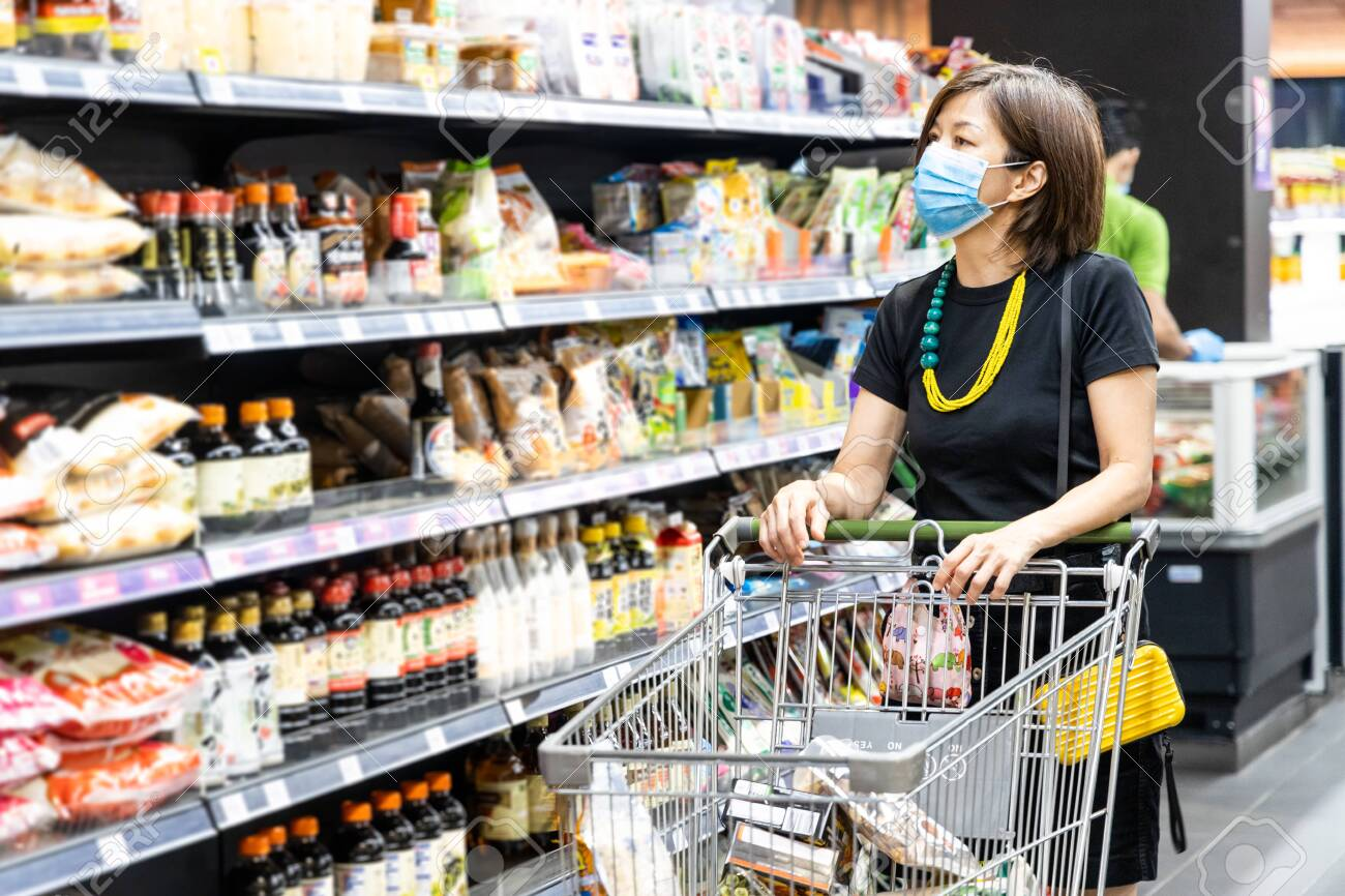 Asian woman shopping groceries in supermarket with protective face mask as new normal requirement in Malaysia - 147729707