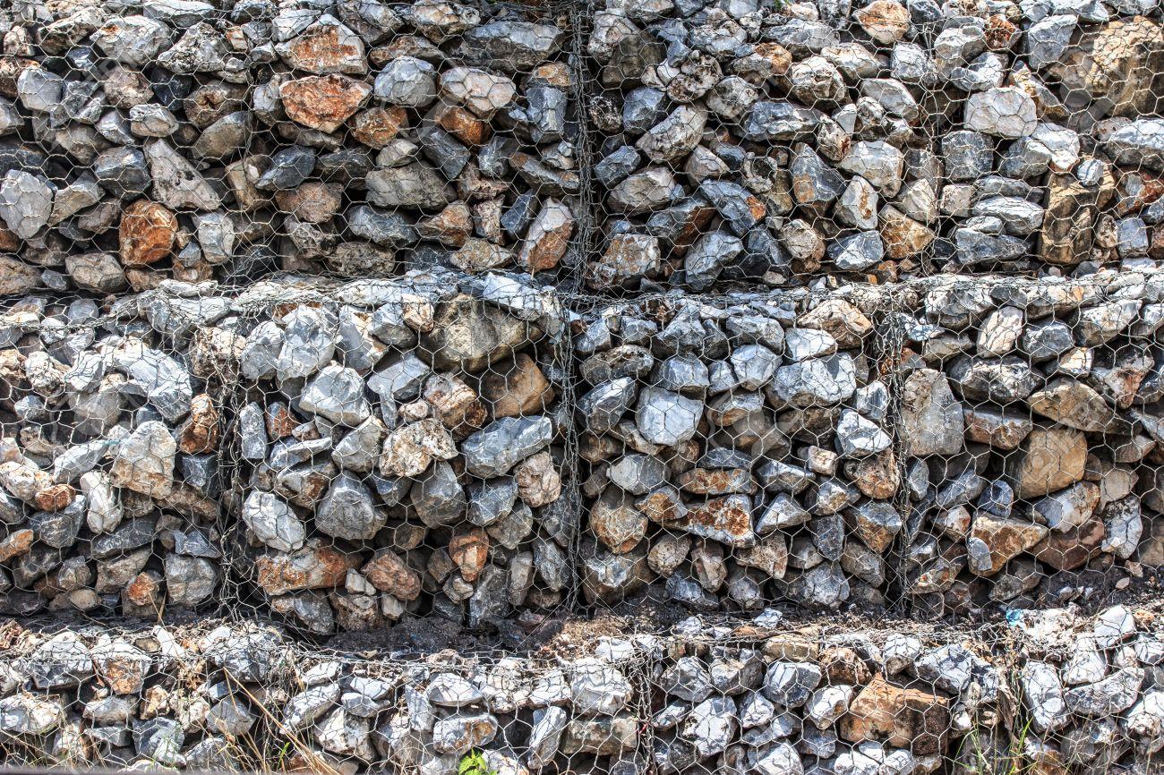 las piedras naturales en mantener una malla de acero muro de gaviones foto de archivo