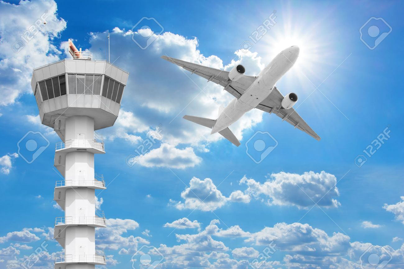 Passenger aircraft flying above air traffic control tower against blue sky - 66533480